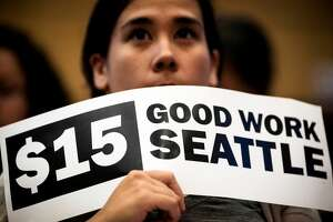 Hoisting signs, supporters showed support for the hopeful passage of the 15-dollar-an-hour minimum wage for Seattle employers Monday, June 2, 2014, at City Hall in Seattle. Phased in over the next seven years, Seattle will have the highest minimum wage in America. (Jordan Stead, seattlepi.com)