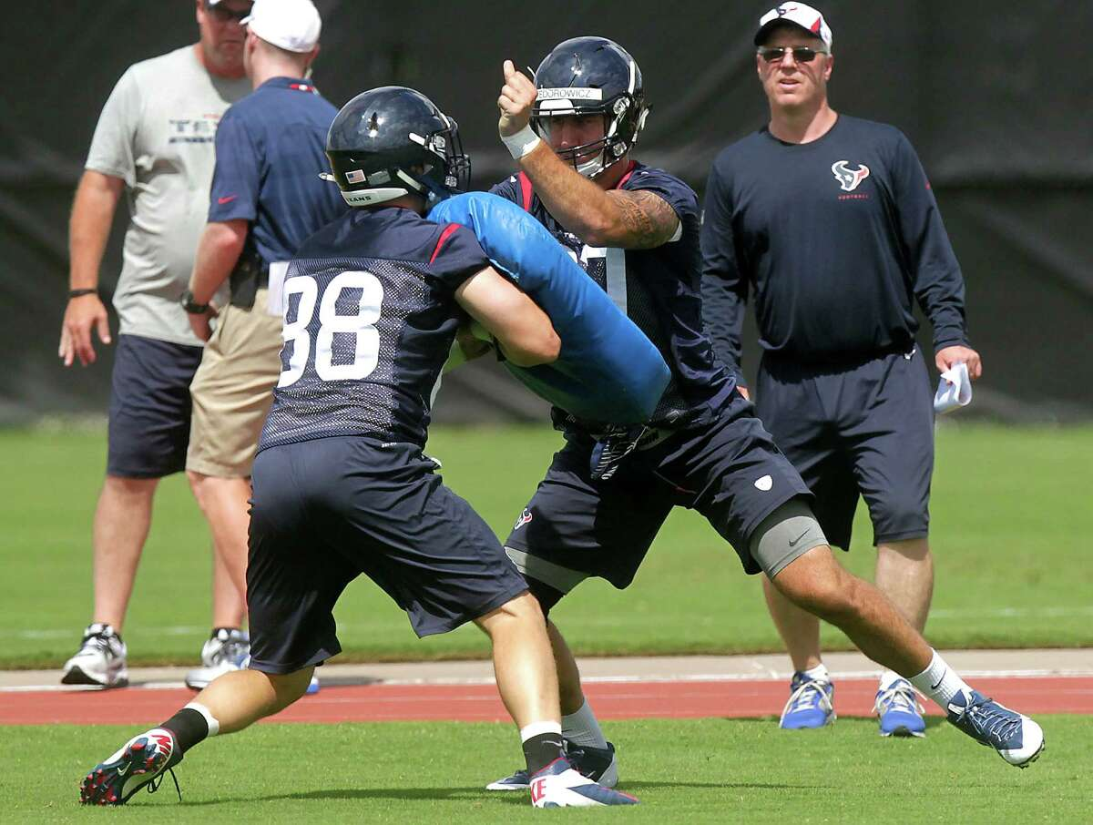 Tight ends Garrett Graham, left, the Texans' veteran at the position going into his fifth NFL season, and rookie C.J. Fiedorowicz, a third-round draft pick, mix it up at Monday's workout.