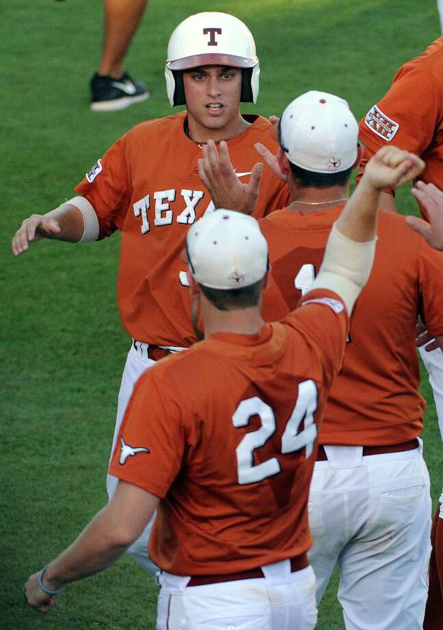 Texas' Madison Carter, top, celebrates his go-ahead run during the fourth inning of an NCAA baseball regional game against Texas A&M, Monday, June 2, 2014, at Reckling Park in Houston. Photo: Eric Christian Smith, For The Chronicle
