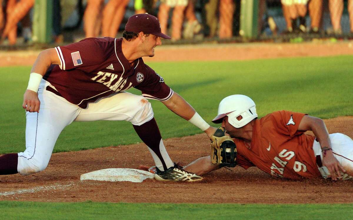 Texas' C.J. Hinojosa, right, is tagged out in a steal attempt of third base by Texas A&M third baseman Logan Nottebrok during the sixth inning of an NCAA baseball regional game, Monday, June 2, 2014, at Reckling Park in Houston.