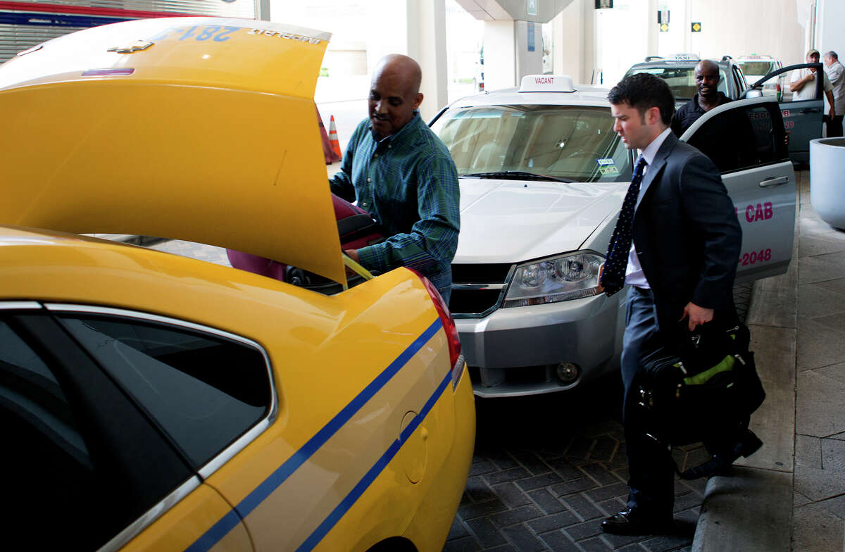 A taxi driver loads luggage at Bush Intercont-inental Airport on Monday. Houston City Council will soon consider a measure to expand the city's taxi services.