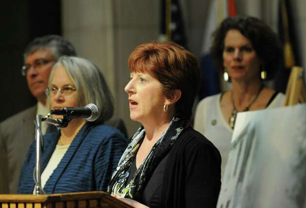 Mayor Kathy Sheehan, center, was joined by area mayors and legislators who spoke in favor of a bill aimed at cracking down on so-called zombie properties Monday, June 2, 2014, during a press conference at City Hall in Albany, N.Y. The new law would force banks and mortgage lenders to properly maintain buildings languishing in the foreclosure process. (Will Waldron/Times Union) Photo: WW / 00027141A