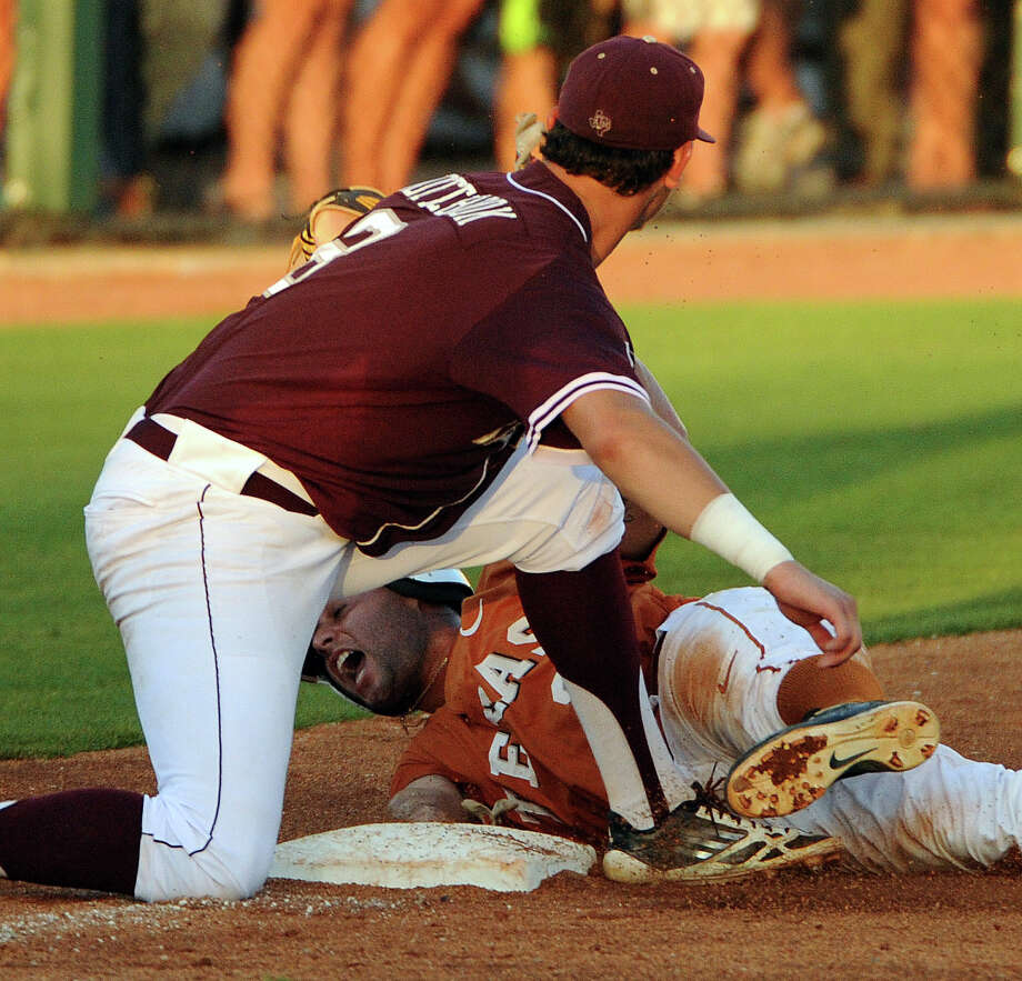 Texas' C.J. Hinojosa, bottom, is tagged out in a steal attempt of third base by Texas A&M third baseman Logan Nottebrok during the sixth inning of an NCAA baseball regional game, Monday, June 2, 2014, at Reckling Park in Houston. Photo: Eric Christian Smith, For The Chronicle