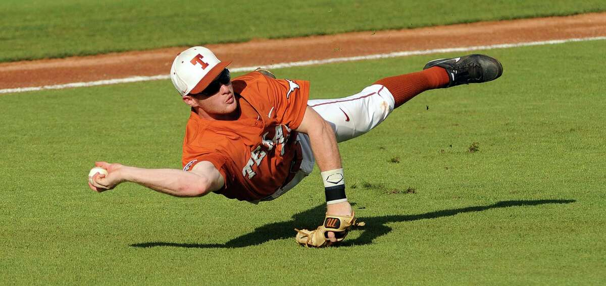 Texas third baseman Zane Gurwitz attempts to throw to first base during the first inning of an NCAA baseball regional game against Texas A&M, Monday, June 2, 2014, at Reckling Park in Houston.