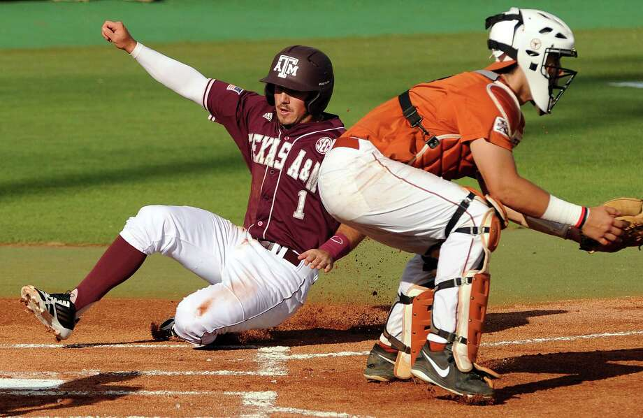 Texas A&M's Blake Allemand, left, slides safely into home past Texas catcher Tres Barrera for the Aggies' first run of the game during the first inning of an NCAA baseball regional game, Monday, June 2, 2014, at Reckling Park in Houston. Photo: Eric Christian Smith, For The Chronicle