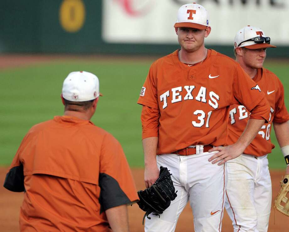 Texas pitching coach Skip Johnson, left, makes his way to the mound to talk with pitcher Chad Hollingsworth after Hollingsworth loaded the bases on a walk during the first inning of an NCAA baseball regional game against Texas A&M, Monday, June 2, 2014, at Reckling Park in Houston. Photo: Eric Christian Smith, For The Chronicle
