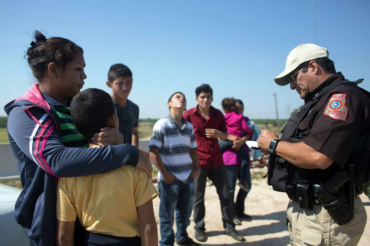 A group of seven people are questioned by a Hildalgo County Hidalgo County Precinct 3 Constable minutes after being smuggled on a raft from Mexico across the Rio Grande River near Anzalduas Dam to Anzalduas County Park Saturday, May 31, 2014, in Mission. The group from El Salvador and Honduras included a mother with her 7-year-old son and a mother with her 4-year-old daughter, an 11-year-old boy and two 17-year-olds, who said they were heading to Houston and Maryland. ( Johnny Hanson / Houston Chronicle )