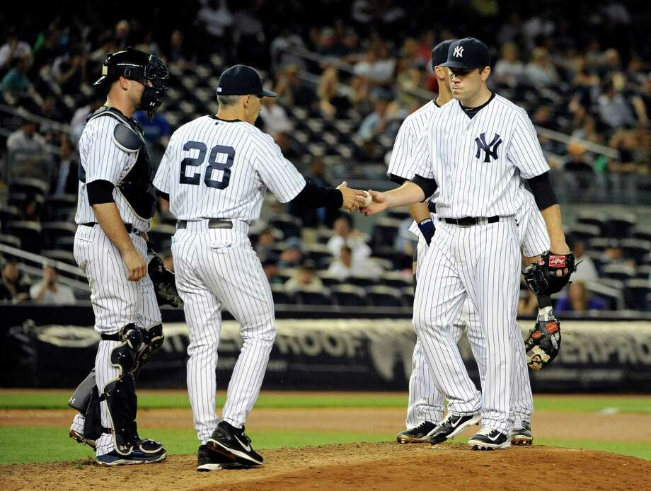 New York Yankees catcher Brian McCann, left,  watches manager Joe Girardi (28) take pitcher David Phelps out of the baseball game after two runs score in the seventh   inning of a baseball game against the Seattle Mariners at Yankee Stadium on Monday, June 2, 2014, in New York. (AP Photo/Kathy Kmonicek) ORG XMIT: NYY125 Photo: Kathy Kmonicek / FR170189 AP