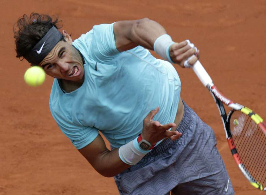 Rafael Nadal hits a return to Dusan Lajovic in their French Open round of 16 match at Roland Garros. Nadal's 6-1, 6-2, 6-1 straight-set win was his record 32nd consecutive at the event. Photo: Kenzo Tribouillard / Getty Images / AFP PHOTO