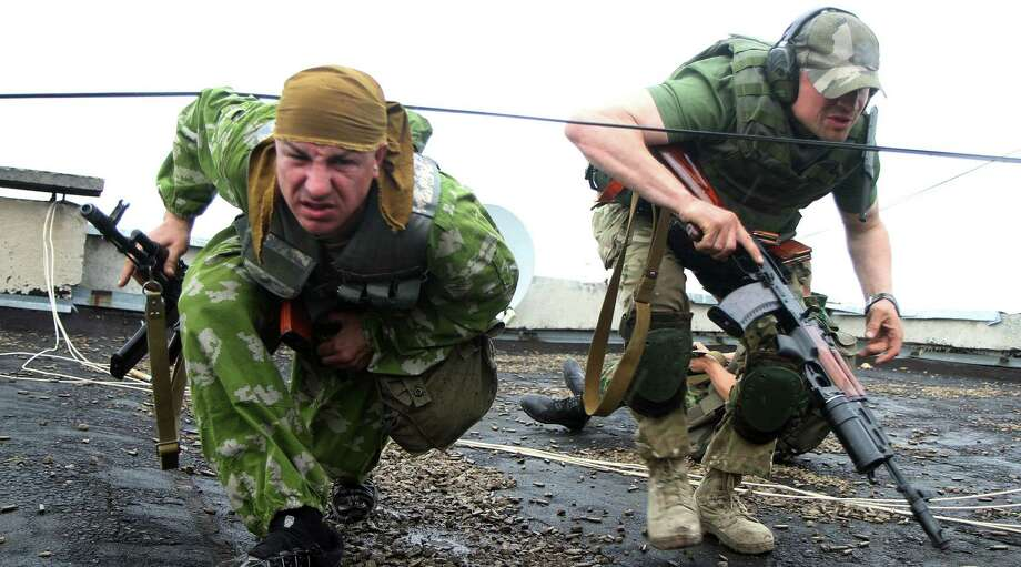 Gunmen described as pro-Russia insurgents militants crouch on a roof fighting with Urkainian guards in the eastern border town of Lugansk. Photo: AFP/Getty Images / AFP