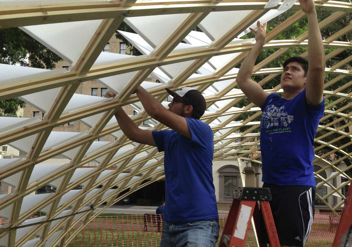 Grad students from UTSA's College of Architecture work on the project. Recent rains helped them bend the wood to fit.
