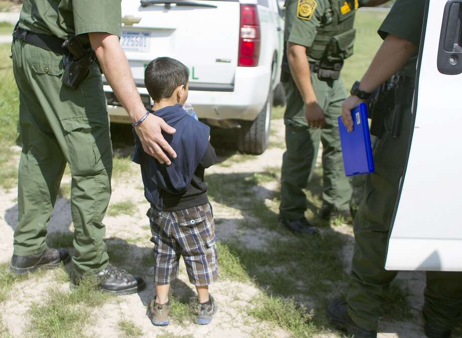 """A 4-year-old boy from Honduras approached a police officer in Anzaldulas Park in 2014 after crossing the Rio Grande from Mexico in  Mission. Child welfare advocates blamed the surge of unaccompanied  children that year to a growing """"humanitarian crisis"""" caused by rampant  gang and cartel violence in Central America. Photo: Johnny Hanson/Houston Chronicle"""