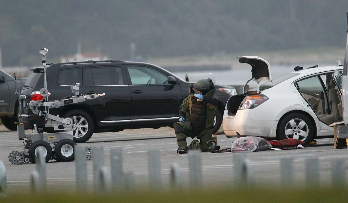 A bomb squad member with the help of a robot investigates the automobile that Ryan Chamberlain was arrested in at Crissy Field in San Francisco on Monday, June 2, 2014.
