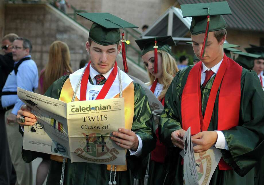 Graduates Griffin Jones and Connor Jones, no relation, read the school paper, the Caledonian, as they march into the Pavilion during The Woodlands High School graduation ceremony at the Cynthia Mitchell Pavilion. Almost 1,000 graduates crossed the stage to receive their diploma.  Photo: David Hopper, For The Chronicle / freelance