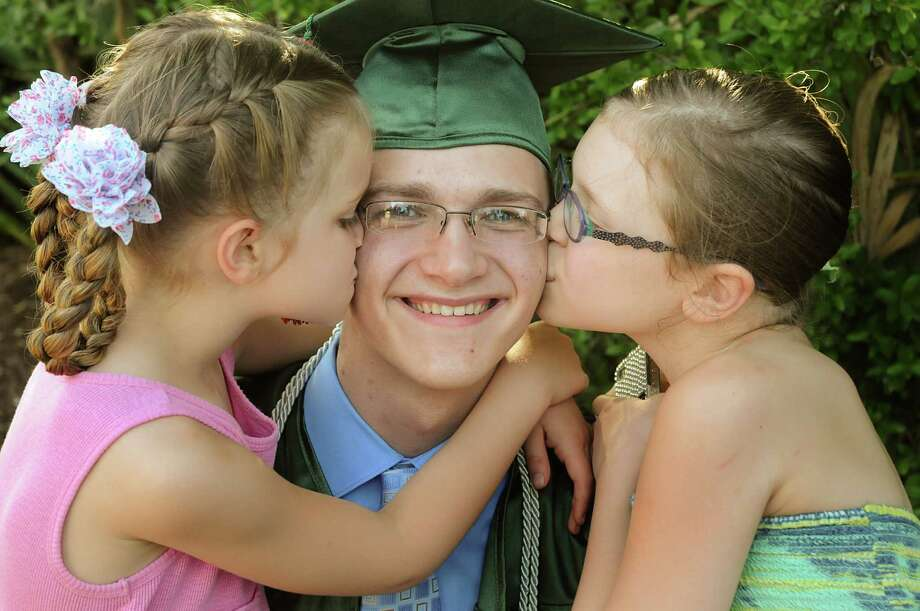 Graduate Cody Baker receives kisses from his little sisters Abagail and Kristian, before The Woodlands High School graduation ceremony at the Cynthia Mitchell Pavilion. Almost 1,000 graduates crossed the stage to receive their diploma.  Photo: David Hopper, For The Chronicle / freelance