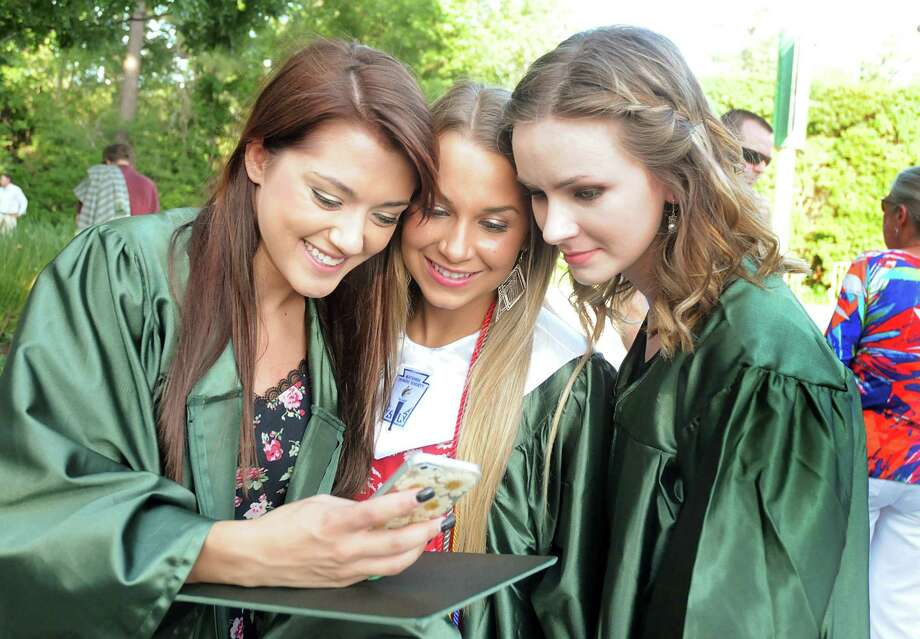 """Graduates Paige Clardy, Sabrina Leonardi, and Ema Ruzic, admire their """"selfie"""" before The Woodlands High School graduation ceremony at the Cynthia Mitchell Pavilion. Almost 1,000 graduates crossed the stage to receive their diploma.  Photo: David Hopper, For The Chronicle / freelance"""