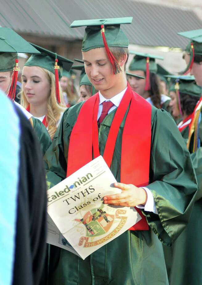 Graduate Connor Jones reads the school paper's, the Caledonian, graduation edition as he marches in to the Pavilion during The Woodlands High School graduation ceremony at the Cynthia Mitchell Pavilion. Almost 1,000 graduates crossed the stage to receive their diploma.  Photo: David Hopper, For The Chronicle / freelance