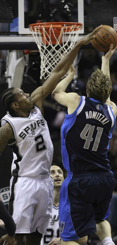 Kawhi Leonard, trying to block a shot by Dallas' Dirk Nowitzki, was voted to the second five on the NBA's All-Defensive team. Photo: Kin Man Hui / San Antonio Express-News / ©2014 San Antonio Express-News