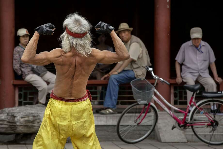 In Beijing, you need a permit for everything:An elderly Chinese man flexes as he performs a martial 