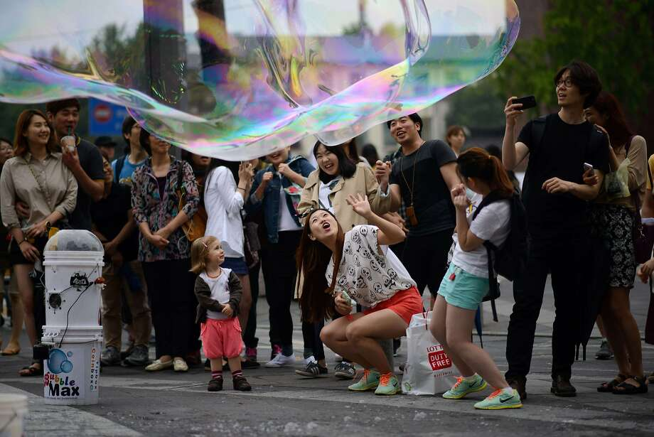 Bubble trap:A large soap bubble created by a street performer lands on tourists in Seoul. Photo: Ed Jones, AFP/Getty Images