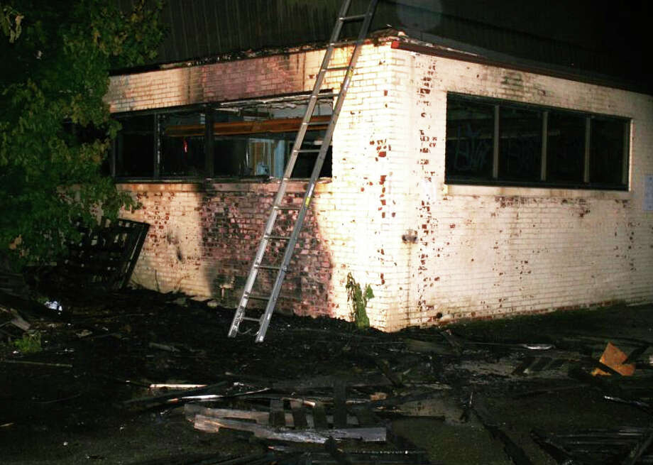 Scene of damage caused by fire in an alley outside Planet Fitness gym and a warehouse off lower Black Rock Turnpike on Monday night. Photo: Fairfield Fire Department / Fairfield Citizen