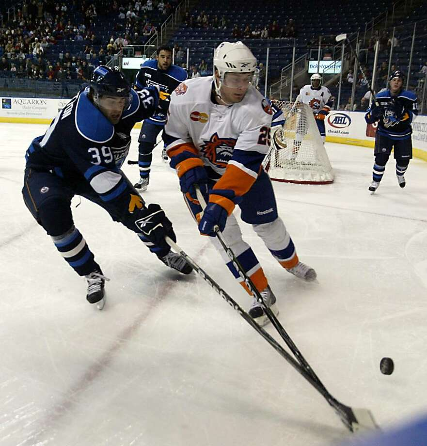 (L-R) Springfield Falcon, Jason Pitton and Soundtiger Ryan Kinasewich go for loose puck during the Soundtigers loss to Springfield, Sunday, Feb. 14, 2010. Photo: Phil Noel / Connecticut Post