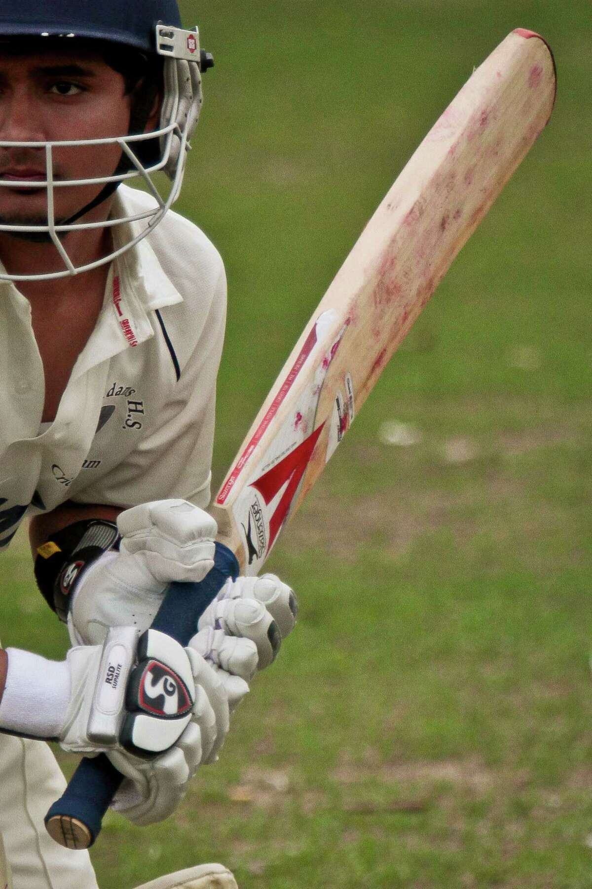 Cricket is surging in popularity around the country. In New York, there aren't enough fields to accommodate all the matches as more and more immigrants from cricket-playing countries move to the U.S. bringing their love for the game with them. In this May 12, 2014 photo, John Adams High School batsman Tazul Uddin raises his bat during a warm-up before playing against Midwood High School in a Public School Athletic League cricket match at Marine Park in the Brooklyn borough of New York. The bat typically consists of a cane handle for gripping attached to a flat-fronted willow-wood blade, treated with raw linseed oil, for striking the ball. (AP Photo/Bebeto Matthews) ORG XMIT: NYBM704