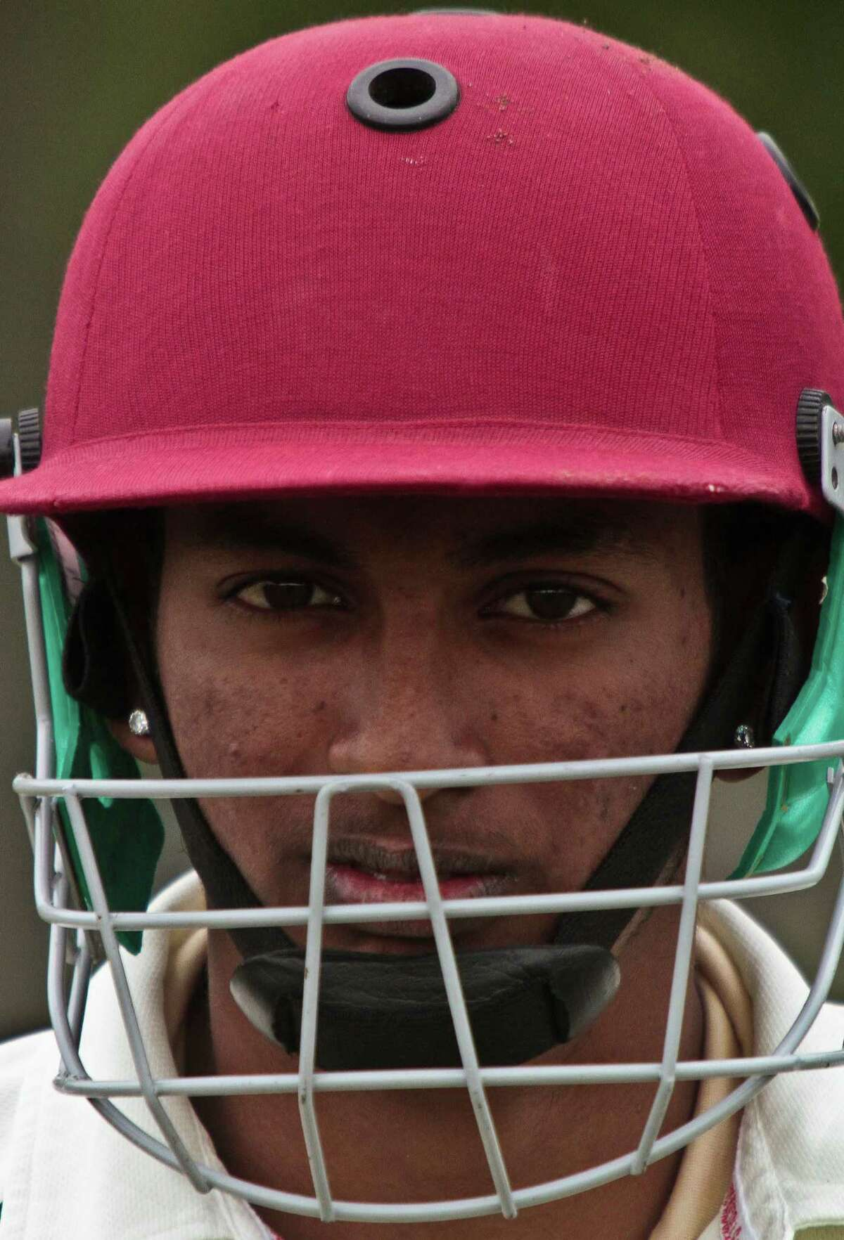 In this May 12, 2014 photo, Derick Narine, currently the top cricket player in the Public School Athletic League (PSAL) from John Adams High School, wears a helmet as he prepares to bat in a match against Midwood High School at Marine Park in the Brooklyn borough of New York. Narine, a junior from Guyana and a member of its under-19 national squad, scored over 50 runs in a 112-80 win. The helmet helps avoid injury as batters try to score runs off a hard cricket ball bowled at speeds that often reach over 90 mph. (AP Photo/Bebeto Matthews) ORG XMIT: NYBM715