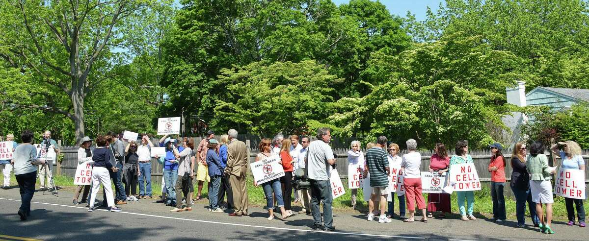 """Opponents of a plan to erect a 120-foot-tall cell phone tower at 92 Greens Farms Road picket against the proposal Tuesday morning while a """"balloon test"""" for the project was conducted."""