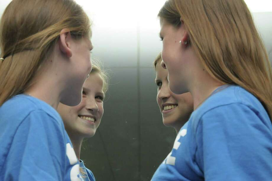 Emily and Caitlin Copeland are reflected in a mirror at Lutheran High North Wednesday, May 14, 2014. Photo: Â Tony Bullard 2014, Freelance Photographer / © Tony Bullard & the Houston Chronicle
