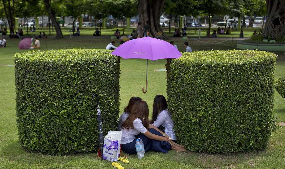 If the heat's getting to you in Yangon, prop your umbrella between a pair of well-manicured shrubberies and climb under it with all your friends. Photo: Gemunu Amarasinghe, Associated Press