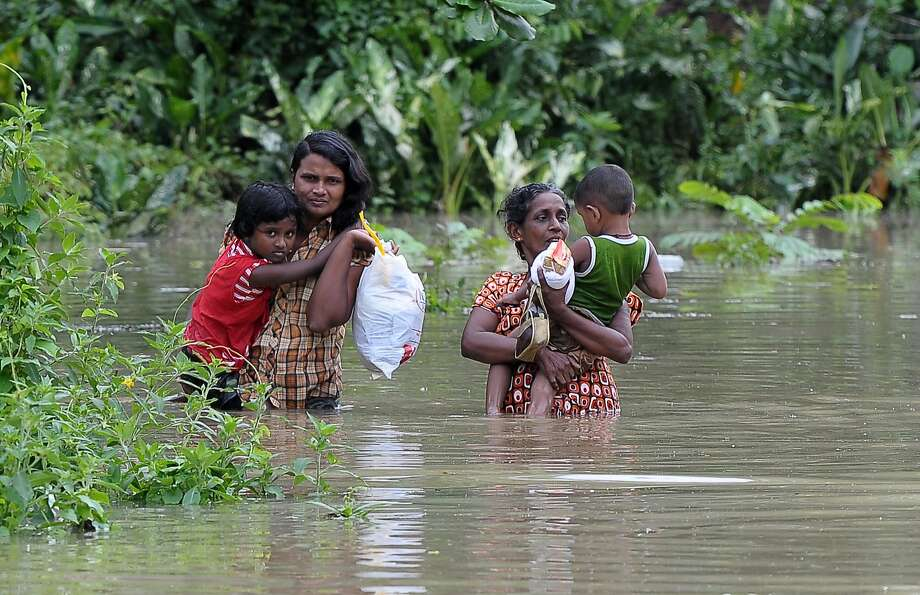 After the deluge:A Sri Lankan family wades through floodwaters in Matugama following heavy monsoon rains that wreaked havoc in the 