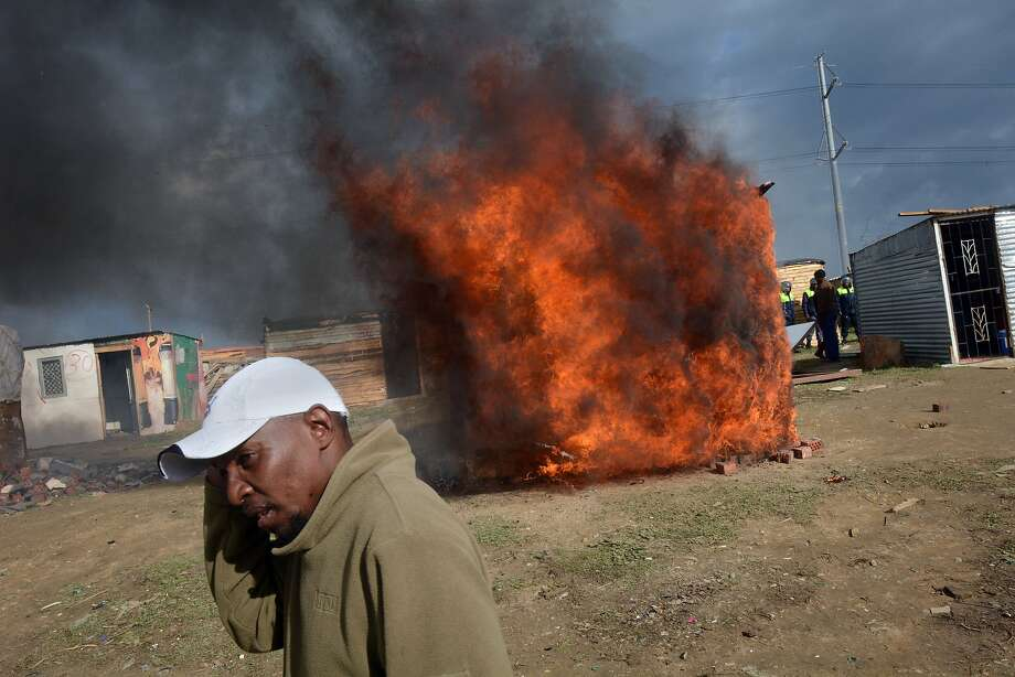 A makeshift house burnsin Lwandle, an impoverished area about 25 miles from Cape Town, as government workers evict squatters from privately owned land earmarked for a highway construction project. Some residents set fire to their homes rather than let workers tear them down. Photo: Rodger Bosch, AFP/Getty Images