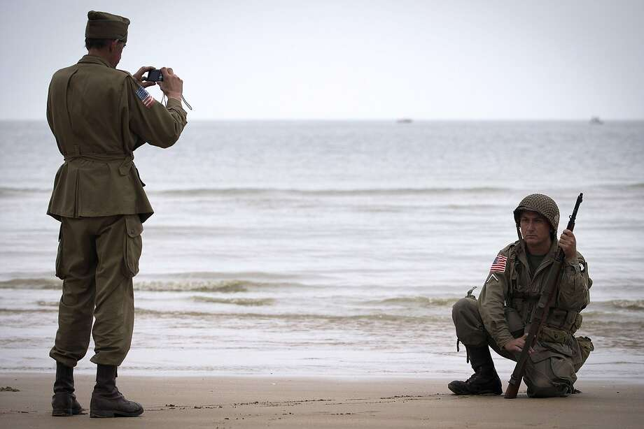 Seventy years after Operation Overlord:On Vierville-sur-Mer beach, one of the D-Day landing beaches in Normandy, a man wearing the uniform of a U.S. soldier sits for a portrait photo. June 6 is the 70th anniversary of the D-Day landings. Photo: Joel Saget, AFP/Getty Images