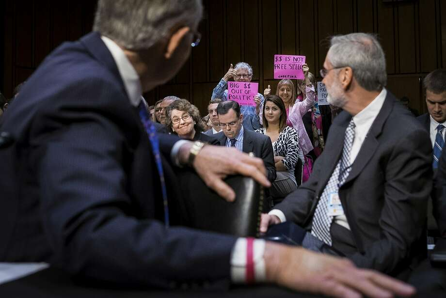Code Pink activists hold up signs in support of a proposed constitutional amendment on campaign finance during a Senate Judiciary Committee hearing in Washington, D.C., U.S., on Tuesday, June 3, 2014. The U.S. Senate's top party leaders clashed at an unusual Judiciary Committee hearing over a proposed constitutional amendment that would give Congress more authority to regulate federal campaign spending. Photographer: Pete Marovich/Bloomberg Photo: Pete Marovich, Bloomberg