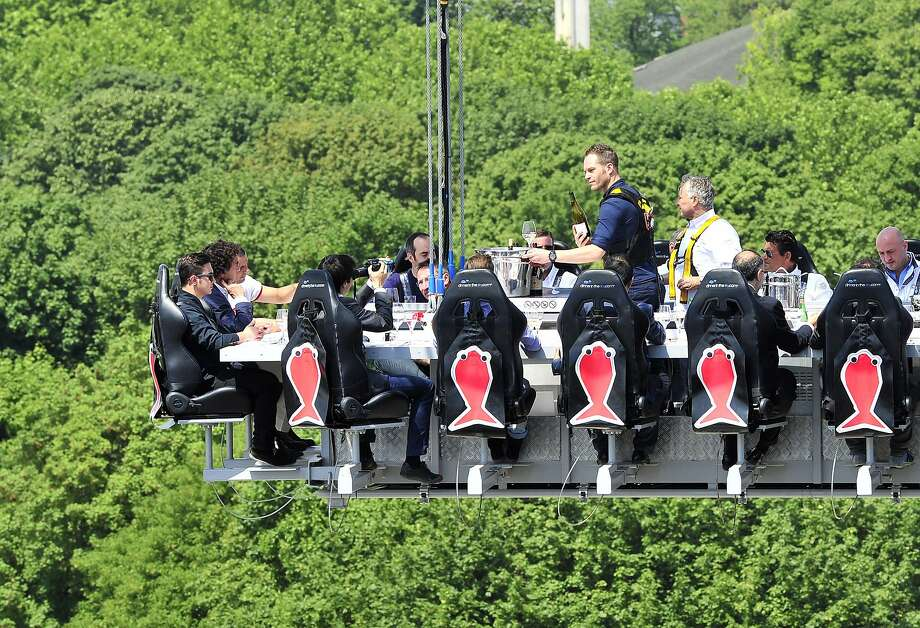 "High cuisine in Brussels:Diners enjoy ""dinner in the sky"" suspended above the Parc du Cinquantenaire in Brussels. Twenty-two guests sit around a mini kitchen where a ""starred"" chef prepares and serves the meals and wine. The only downside - you can't leave the table to go to the restroom. Photo: Georges Gobet, AFP/Getty Images"
