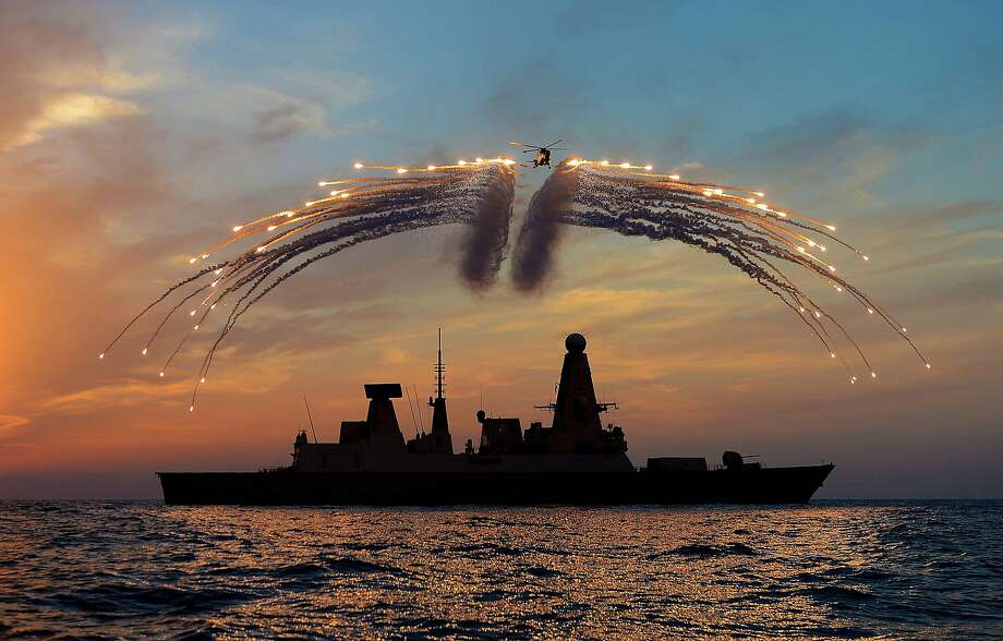 Dragon fire: A British Lynx Mk8 helicopter fires all 60 of its flares at once over the destroyer HMS Dragon during war games off Portsmouth, England. The picture won a prize in the Royal Navy's photographic awards. Photo: Dave Jenkins, AFP/Getty Images