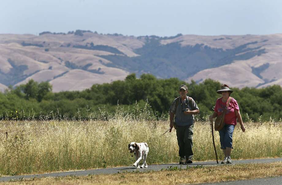 Hikers walk on a trail through privately owned land in Fremont that will soon be a part of the East Bay Regional Park District. Photo: Paul Chinn, The Chronicle