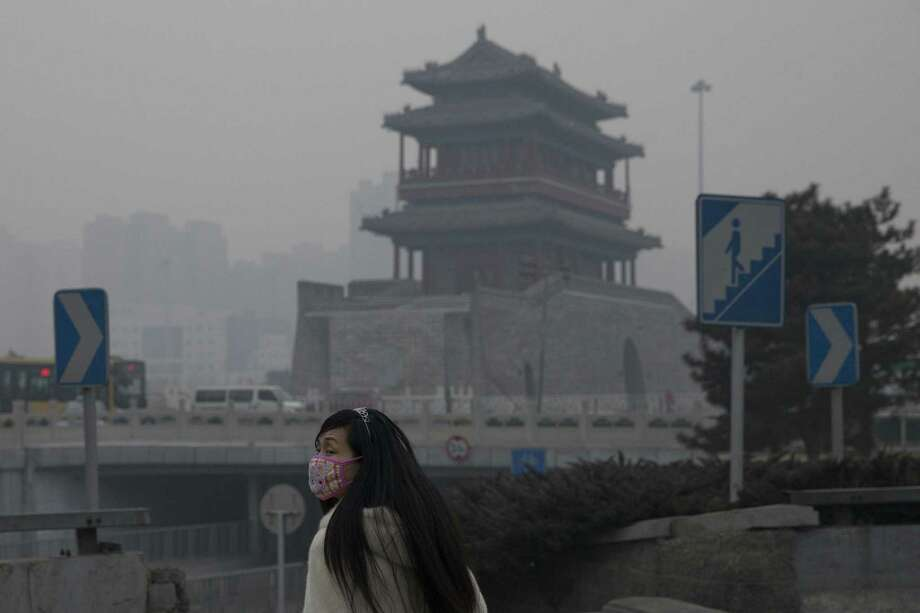 A woman wears a mask as she walks under smog in Beijing. Chinese officials face the challenge of reducing carbon emissions produced largely by coal-fired power plants; perhaps they will be influenced by President Barack Obama's initiative this week. Photo: Alexander F. Yuan / Associated Press / AP