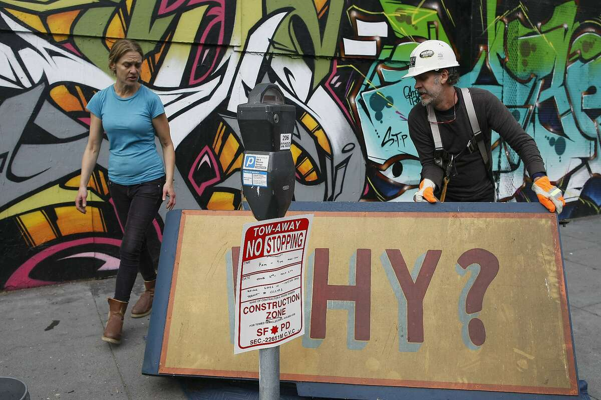 Catherine Morgan, left, and Brian Goggin reposition a sign after taking it off the Hotel Hugo on Howard and 6th St. in San Francisco, Calif. on Tuesday, June 3, 2014. The work by Brian Goggin has remained on the building for 17 years.