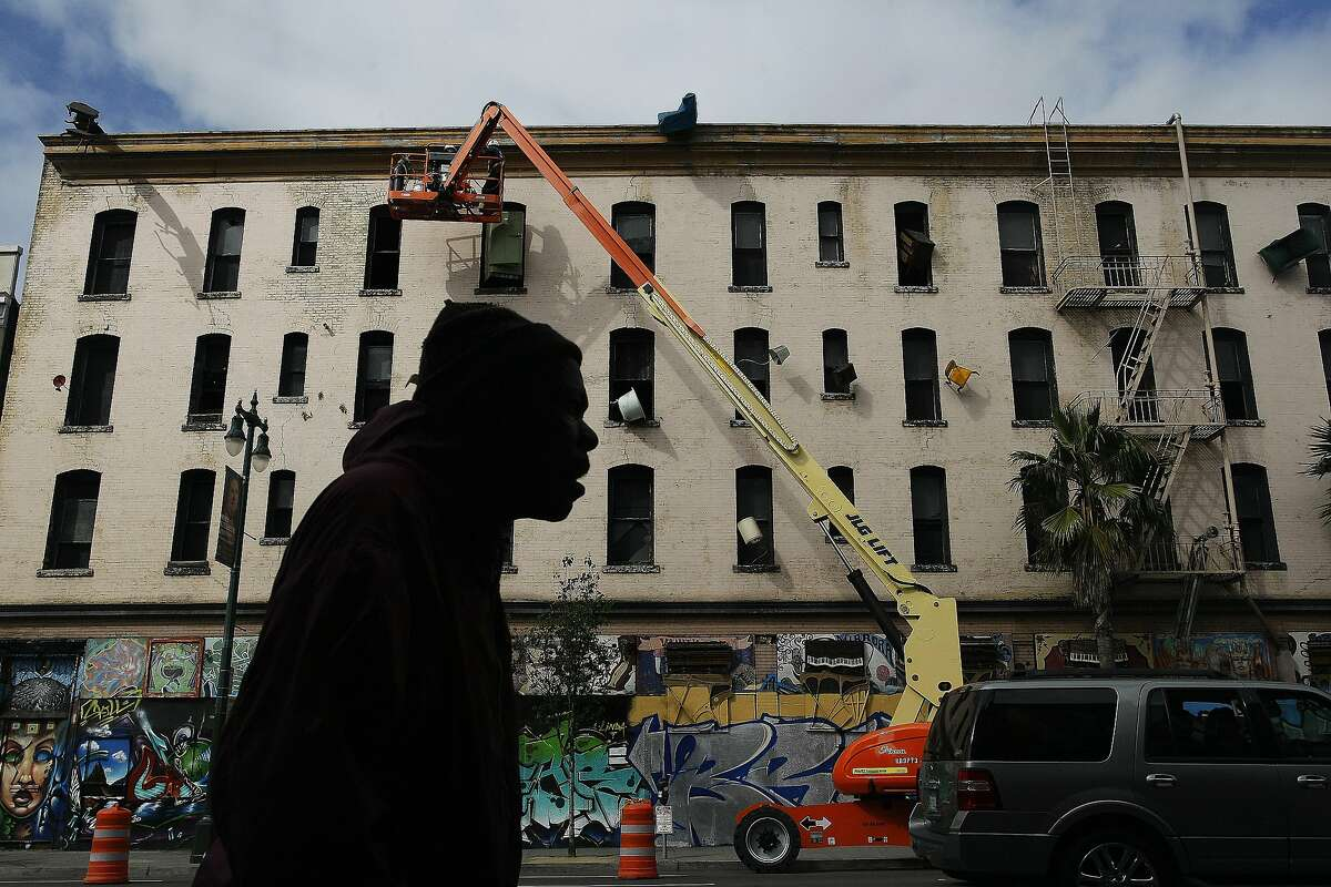 A man passes by workers taking furniture off the side of the Hotel Hugo on Howard and 6th St. in San Francisco, Calif. on Tuesday, June 3, 2014. The work by Brian Goggin has remained on the building for 17 years.