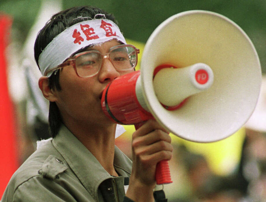 "Chinese dissident Wang Dan addresses fellow students during a demonstration in Beijing's Tiananmen Square, in this May 1989  photo.  The characters on Wang's headband translate as ""hunger strike.""  Fifteen years after the bloodshed, the exiled student leaders of China's 1989 pro-democracy protesters are settled abroad as academics and entrepreneurs. But they nurture one with above all - to come home to a new system. Wang Dan, a principal strategist for the protests, spent seven years in prison. Now 35, he is working toward a doctorate at Harvard University with a thesis on Chinese politics and history and the democratic movement in Taiwan. Photo: ASSOCIATED PRESS / AP1989"