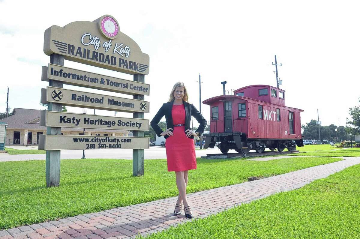 Katy Kayce Reina stands in front of Katy's railroad museum with its signature caboose, antique shops and restaurants.