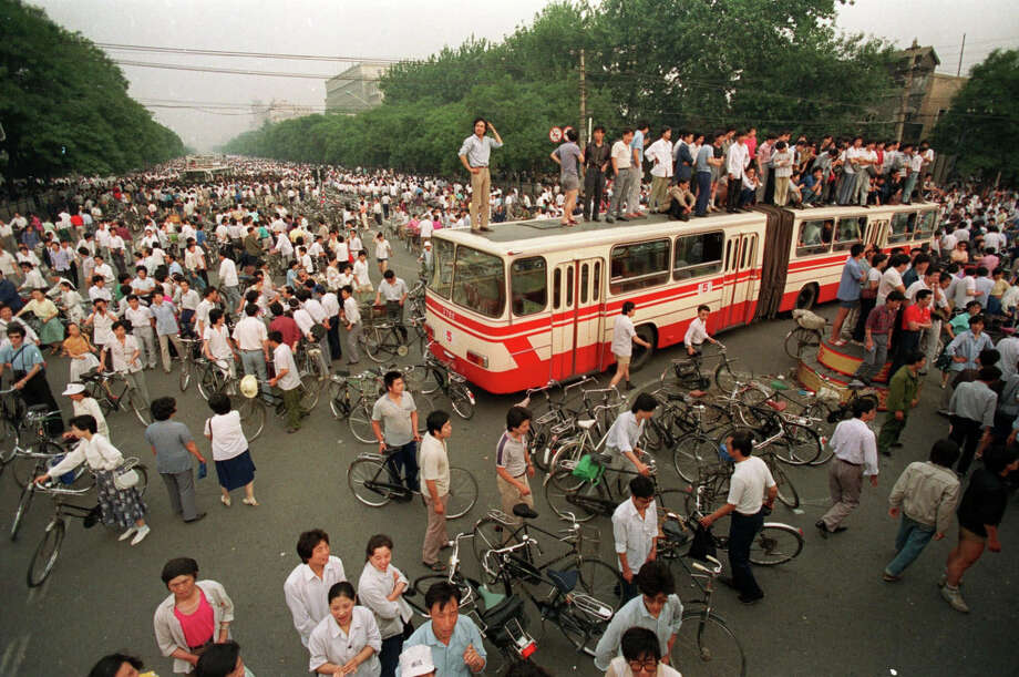 A huge crowd gathers at a Beijing intersection where residents used a bus as a roadblock to keep troops from advancing toward Tiananmen Square in this June 3, 1989 photo. Friday June 4, 1999 is the 10th anniversary of the military assault on pro-democracy protestors who had occupied the square for seven weeks. Hundreds died in the early hours of June 4, 1989 when troops shot their way through Beijing's streets to retake the square. Photo: JEFF WIDENER, AP / 1989 AP