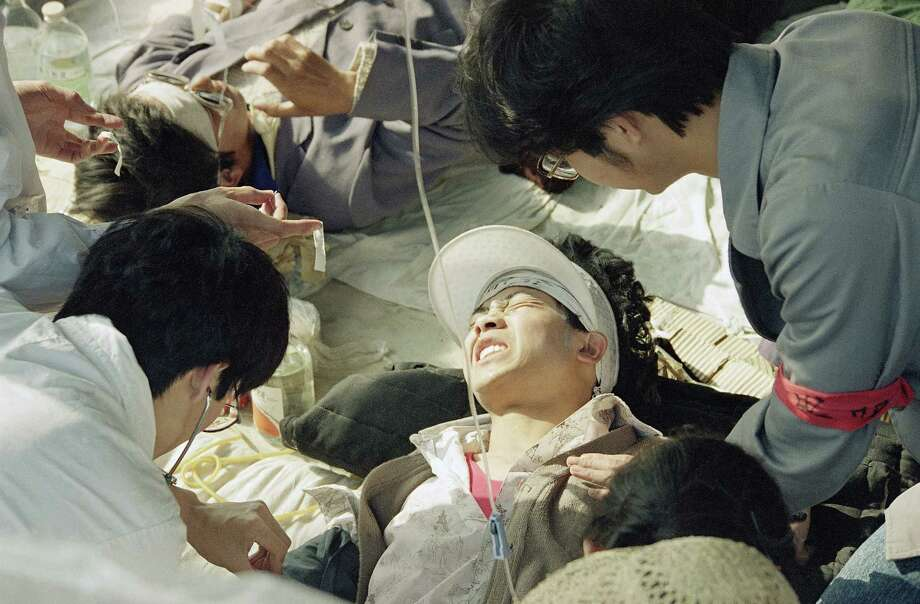 A striking Beijing University student is given first aid by medics at a field hospital in Tiananmen Square at Beijing, Wednesday, May 17, 1989, the fourth day of their hunger strike for democracy. Photo: Sadayuki Mikami, AP / 1989 AP