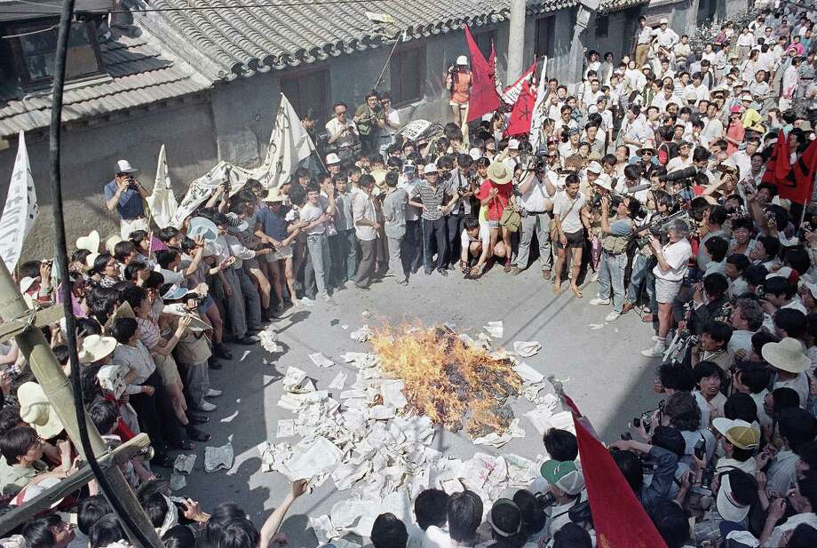 A huge crowd gathers to watch as student protestors burn copies of Beijing Daily in retaliation for anti-student articles in front of the newspaper's offices, Friday, June 2, 1989, Beijing, China. Photo: Jeff Widener, AP / 1989 AP