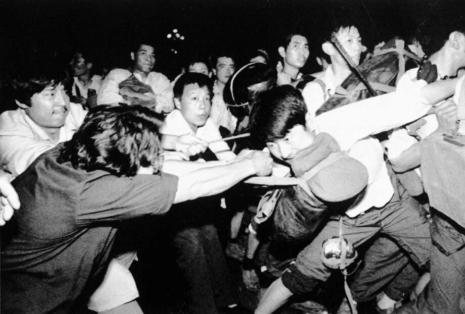 A man tries to pull a Chinese soldier away from his comrades as thousands of Beijing's citizens turned out to block thousands of troops on their way towards Tiananmen Square early Saturday morning, June 3, 1989. Photo: Mark Avery, AP / 1989 AP