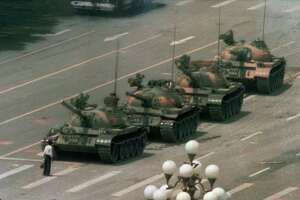 """A Chinese man stands alone to block a line of tanks heading east on Beijing's Cangan Blvd. in Tiananmen Square on June 5, 1989.  The man, calling for an end to the recent violence and bloodshed against pro-democracy demonstrators, was pulled away by bystanders, and the tanks continued on their way.  The Chinese government crushed a student-led demonstration for democratic reform and against government corruption, killing hundreds, or perhaps thousands of demonstrators in the strongest anti-government protest since the 1949 revolution. Ironically, the name Tiananmen means """"Gate of Heavenly Peace."""""""