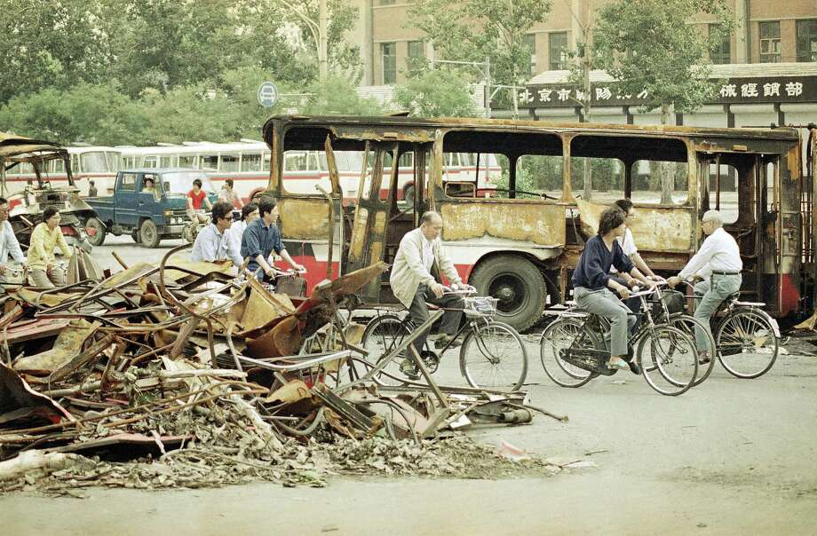 Bicyclists peddle through the ruins of the last weeks battle between the Peoples Liberation Army and students demonstrating for democracy in Tiananmen Square, June 10, 1989, Beijing, China. This scene is located some three miles from the square. Photo: Jeff Widener, AP / 1989 AP