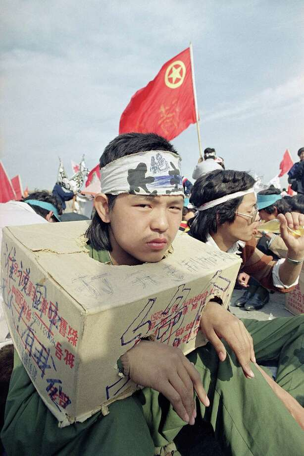 A Beijing university student sits bound in a cardboard box as the strike for democracy continues for the third day in Beijing's Tiananmen Square, Tuesday, May 16, 1989. The box indicates he cannot use his hands so he cannot eat. ( Photo: Sadayuki Mikami, AP / 1989 AP